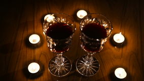 Wine glasses and burning candles. Two glasses of wine on black background and burning candles.Glasses of red wine over candlelight and darkness..Romantic stock footage
