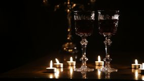 Wine glasses and burning candles. Two glasses of wine on black background and burning candles..Glasses of red wine over candlelight and darkness..Slider video stock video