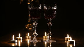 Wine glasses and burning candles. Two glasses of wine on black background and burning candles.Red wine glasses.Glasses of red wine over candlelight and darkness stock footage