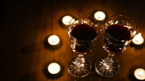 Wine glasses and burning candles. Two glasses of wine on black background and burning candles.Red wine glasses.Glasses of red wine over candlelight and darkness stock video footage
