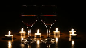 Wine glasses and burning candles. Two glasses of wine on black background and burning candles.Red wine glasses.Glasses of red wine over candlelight and darkness stock video