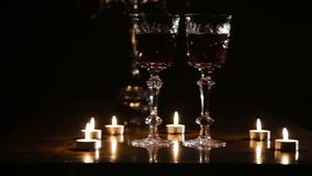 Wine glasses and burning candles. Two glasses of wine on black background and burning candles..Glasses of red wine over candlelight and darkness..Slider video stock footage