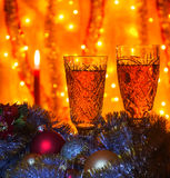 Wine glasses with champagne and a burning candle. Some wine glasses of champagne lying Christmas balls and tinsel. On blurred background is visible burning Royalty Free Stock Image