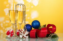 Wine glasses, Christmas decorations and gifts, pine branch, on yellow background. Wine glasses, Christmas decorations and gifts, pine branch, on bright yellow Royalty Free Stock Image