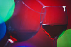 Wine glasses and colorful lights Stock Photos
