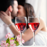 Wine glasses with couple kissing in background. Stock Image