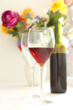 Wine glasses filled with red wine and wine bottle Royalty Free Stock Images