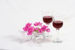Wine glasses and flowers. A still-life of wine glasses with red wine and pink flowers Stock Photography