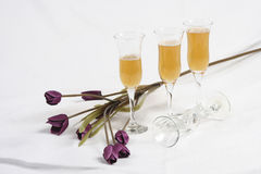 Wine glasses and flowers. Close up of three full wine glasses with fourth lying on side next to purple artificial flowers, still life stock photo