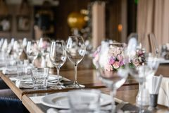 Wine glasses in the foreground. Wedding Banquet or gala dinner. The chairs and table for guests, served with cutlery and. Crockery royalty free stock photo