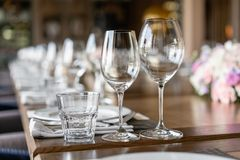 Wine glasses in the foreground. Wedding Banquet or gala dinner. The chairs and table for guests, served with cutlery and. Crockery stock image
