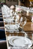 Wine glasses in the foreground. Wedding Banquet or gala dinner. The chairs and table for guests, served with cutlery and. Crockery royalty free stock image