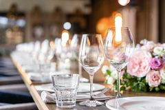 Wine glasses in the foreground. Wedding Banquet or gala dinner. The chairs and table for guests, served with cutlery and. Crockery royalty free stock photography