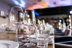 Wine glasses in the foreground. Wedding Banquet or gala dinner. The chairs and table for guests, served with cutlery and. Crockery royalty free stock photos