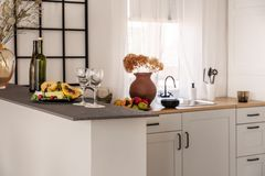 Wine, glasses and fruits on marble kitchen counter in elegant interior with white cupboards.  royalty free stock images