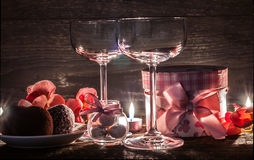 Wine glasses, gift and sweets for a romantic evening Royalty Free Stock Images
