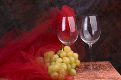 Wine glasses with grapes. Pair of wine glasses with red tulle and a cluster of green grapes stock photos