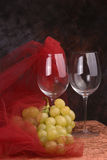 Wine glasses and grapes. Pair of crystal wine glass and bunch of green grapes with red meshed cloth Royalty Free Stock Photography