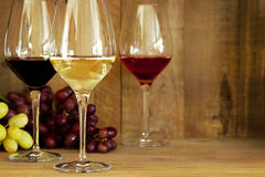 Wine Glasses and Grapes. Wine glasses with grapes, against oak background.  Includes red, white, and rose Stock Photography