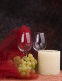 Wine glasses, grapes, candle. A still life display of two wine glasses, a bunch of green grapes and a white candle with red decorations. Black background stock photo