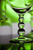 Wine glasses with green background. Colorful wine glass with bubble stem and glasses in soft focus in background royalty free stock image