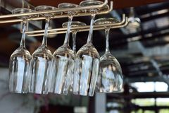 Wine glasses hang on bar rack Royalty Free Stock Images