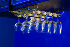 Wine Glasses Hanging Above Bar. In Club Lit with Ultra-violet and Neon Lighting Stock Image