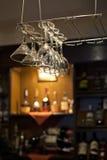 Wine glasses hanging near bar counter Stock Photo