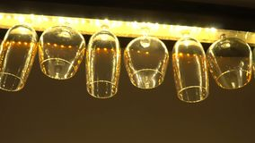 Wine glasses hanging in a row. Under ceiling of a bar stock video footage