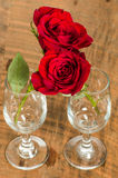 Wine glasses and hugging roses Royalty Free Stock Photo
