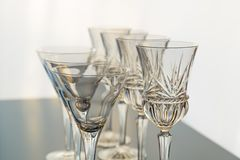Decorative wine and martini glasses are set up in verticle rows displaying beautiful details of the glass. Wine glasses and martini glasses are set up in stock images