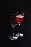 Wine glasses one with red. Backlit wine glasses one full one empty stock photo