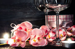 Wine glasses orchids and candles for a romantic evening Royalty Free Stock Photography