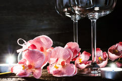 Wine glasses orchids and candles for a romantic evening Stock Photography