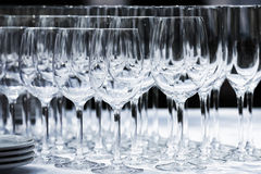 Wine glasses with plates on the table. Black background. Stock Image