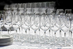 Wine glasses with plates on the table. Black background. Stock Photos