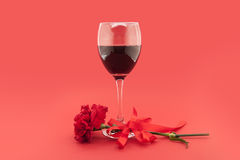 Wine in glasses,  red carnation with white ribbon on red Stock Photography