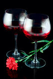 Wine glasses and a red flower Stock Images