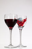 Wine glasses with red wine and golf ball Royalty Free Stock Images