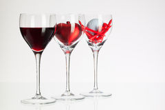 Wine glasses with red wine, heart and golf ball Royalty Free Stock Images