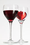 Wine glasses with red wine and heart Stock Images