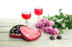 Wine in glasses, roses and a box of sweets on a wooden table Stock Photo