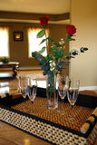 Wine Glasses and Roses on Tray. Four wine glasses and two red roses in a bouquet sit in a serving tray, waiting for the entertainment to begin Royalty Free Stock Photos