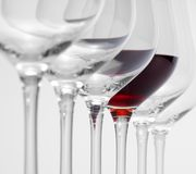 Wine glasses in a row. Some wine glasses standing consecutive in a row in light grey back, one partly filled with red wine stock images