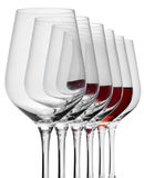 Wine glasses in a row. Some wine glasses standing consecutive in a row in white back, one partly filled with red wine stock image