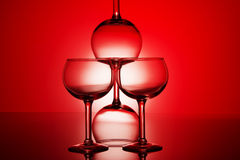 Wine glasses. Silhouetted on a red background artfully set up with spot light behind Stock Photos