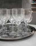 Wine glasses on silver metal tray on white table. royalty free stock photography