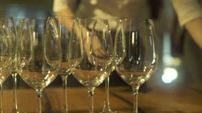 Wine glasses standing on party table in restaurant close up. Empty wine glasses at event table at holiday evening. Wine glasses standing on party table in stock video