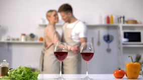 Wine glasses standing on table, loving couple dancing on background, romance royalty free stock image