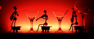 Wine glasses and statuetes in red light Stock Photo